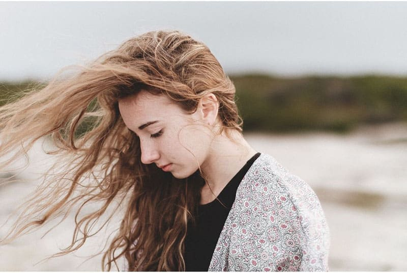sideview of young woman with wavy hair blown by the wind