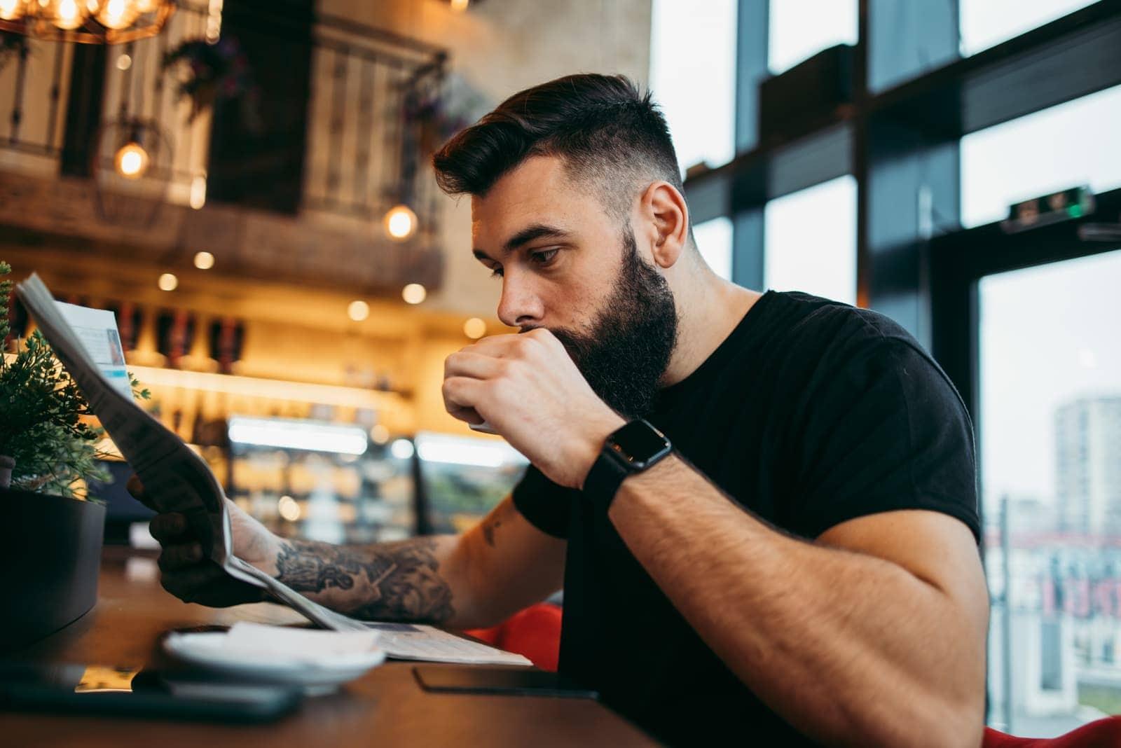 tattooed man sitting in cafe drinking coffee