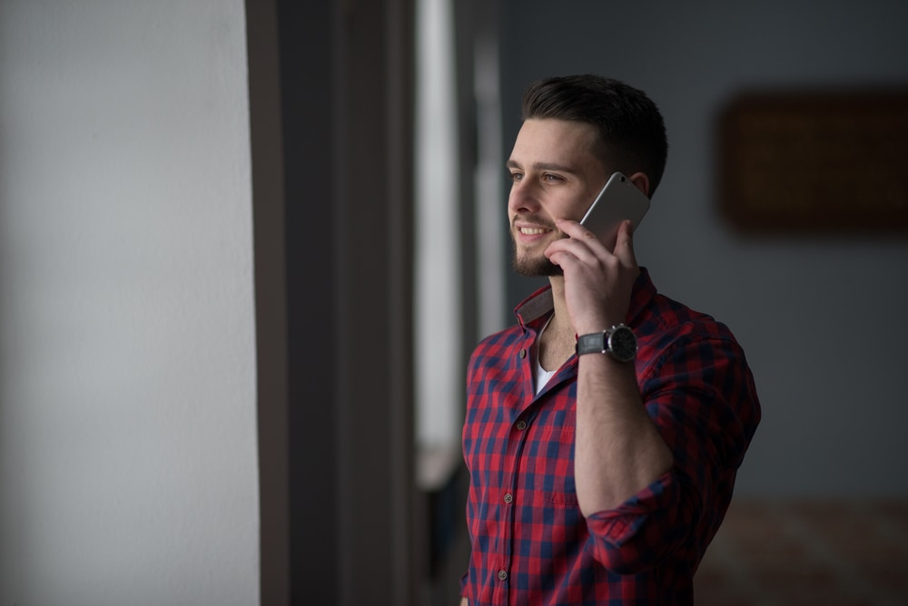 the man stands and talks on the phone