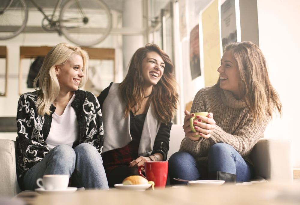 three girls sit drinking coffee laughing and talking