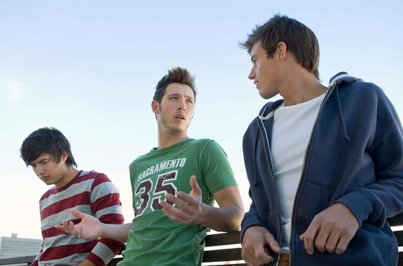 three men talking outdoors with middle person talking