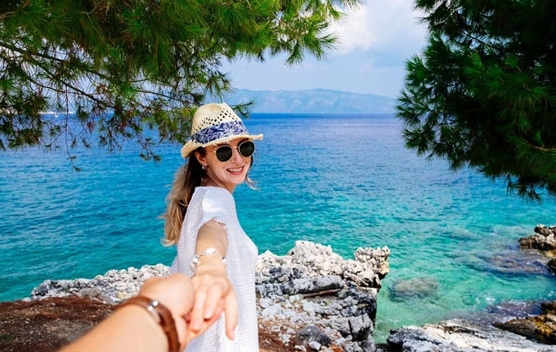 travelling young woman holding hand of a person standing near a blue deep body of water