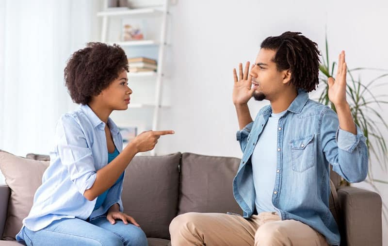 unhappy couple arguing in the sofa inside the living room