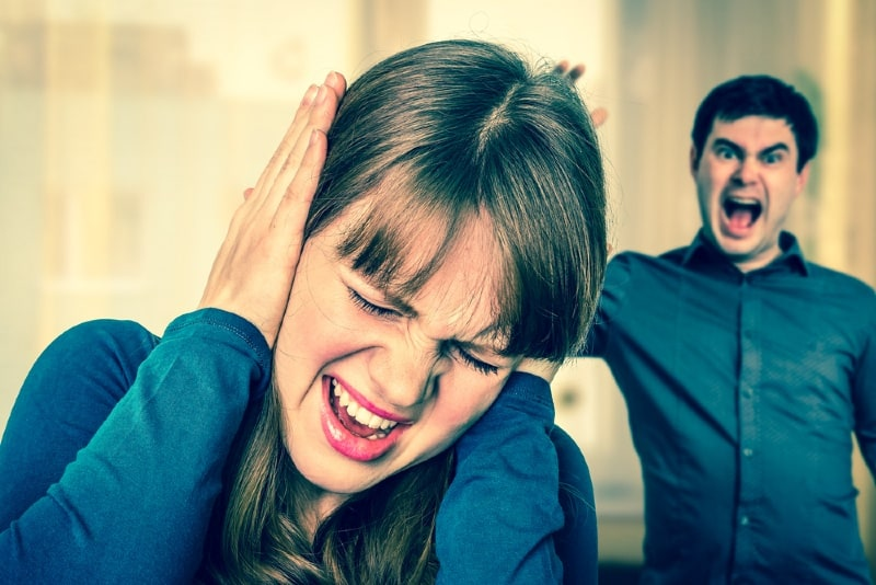 woman covering her ears with her hands while man yelling at her