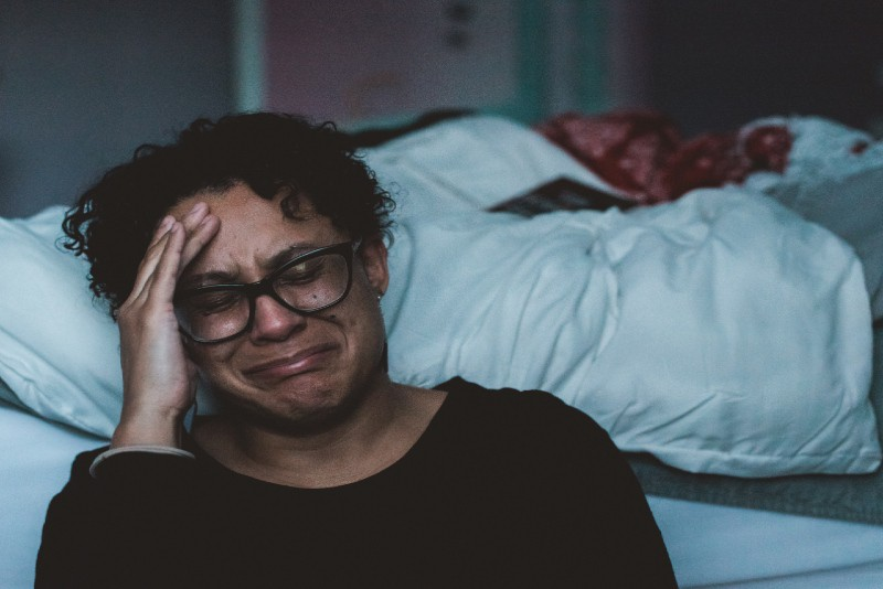 woman in black shirt crying beside bed