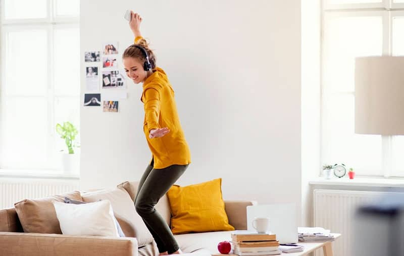 woman dances alone on top of the sofa inside living room