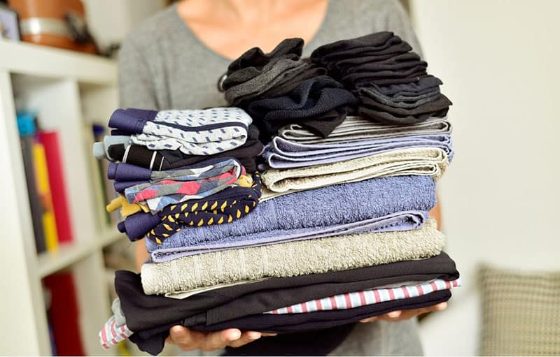 woman declutters wardrobe with a pile of clothes on hand
