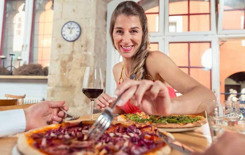 woman eating pizza with fork in her hand trying to get a slice