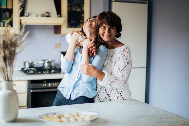 woman embraced by an older woman while standing in the kitchen