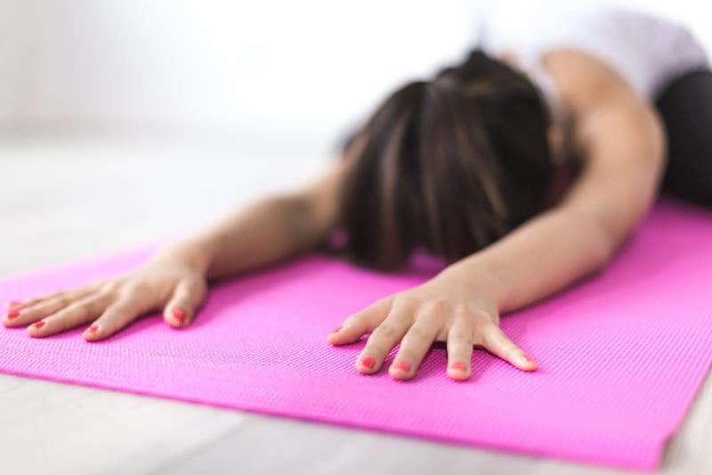 woman exercising yoga on pink mat