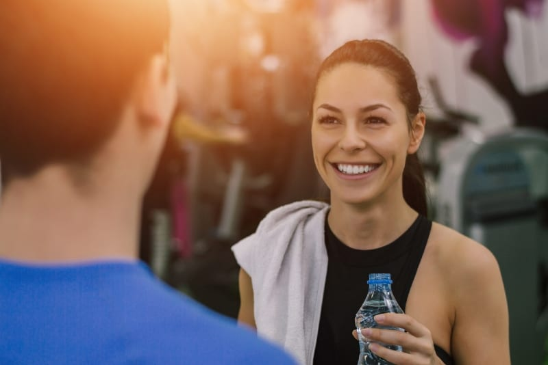 smiling woman holding bottle of water while looking at man
