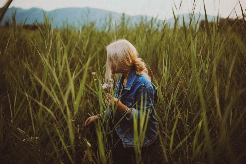 blonde woman holding flowers while standing in the field