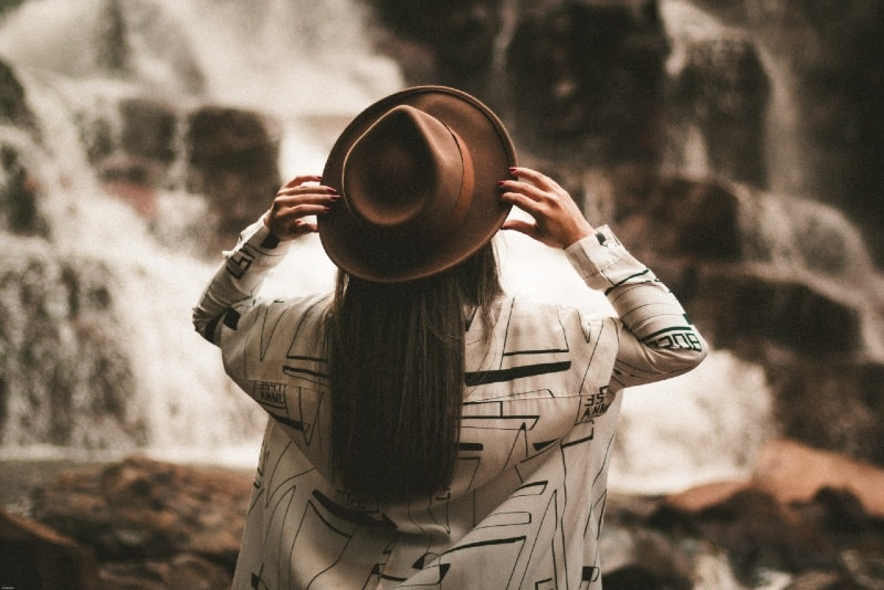 woman holding brown hat while looking at waterfall