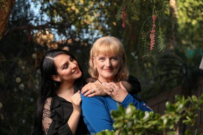 woman hugging woman in blue shirt outdoor