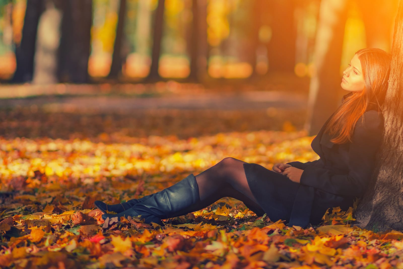 woman in black coat and leather boots sitting under tree in autumn park