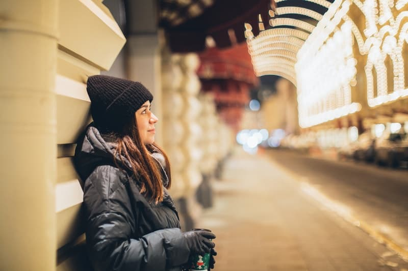 woman in black knit cap and black jacket standing in a public place with lights along the streets