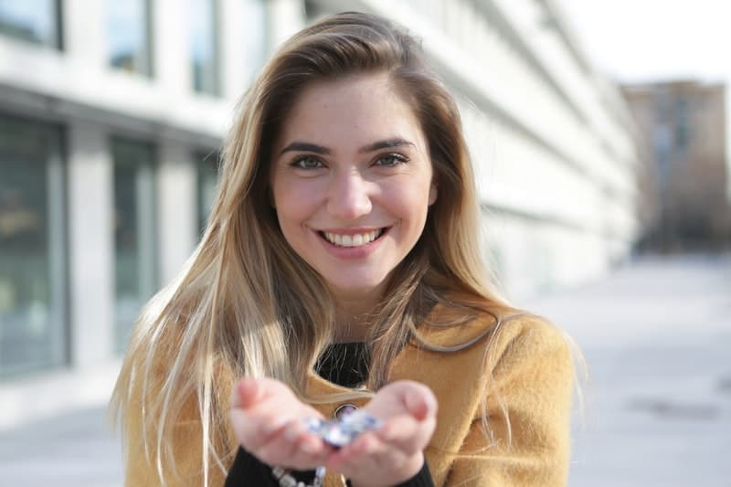 woman in brown sweater smiling holding a blurred gem in her hands