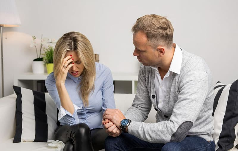 woman in pain sitting next to a man consoling her