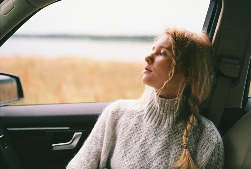 woman in sweater sitting inside the passenger seat of a car