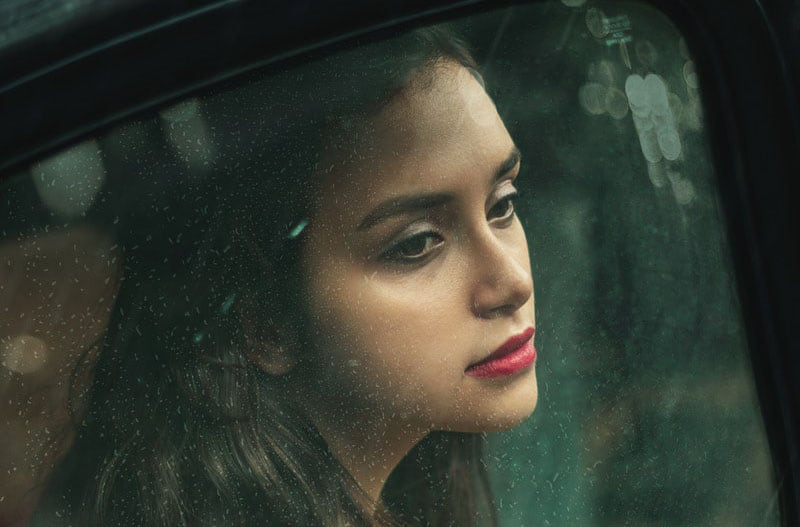 woman inside the car looking outside with face in focus