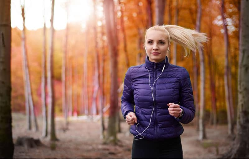 woman jogging in the woods while listening to music thru the earphones