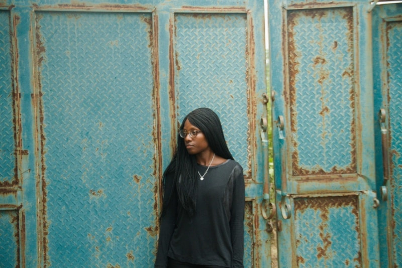 woman in black top leaning on blue door