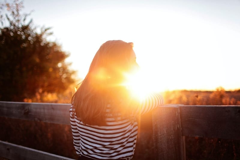 woman leaning on wooden fence during sunset