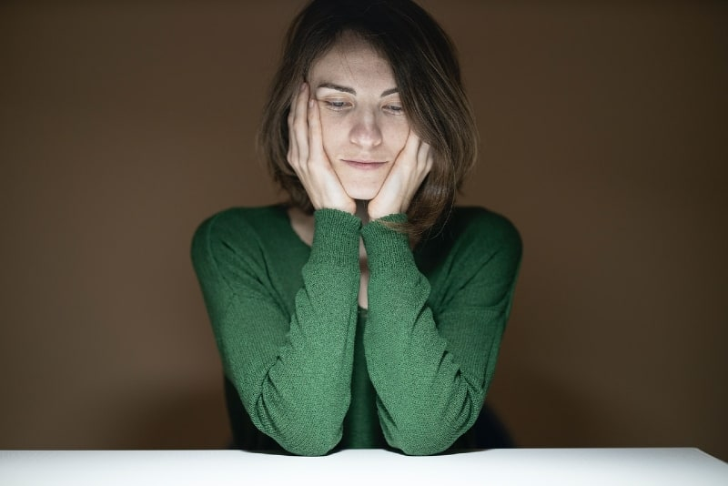 woman in green shirt leaning on table