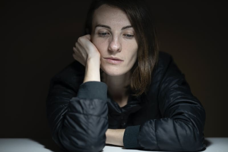 woman in black jacket leaning on table