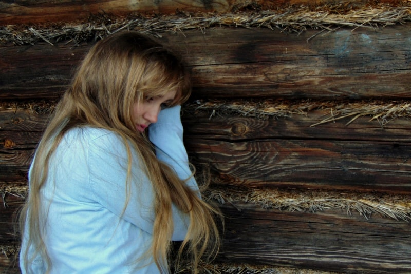 sad woman in white top leaning on wooden wall