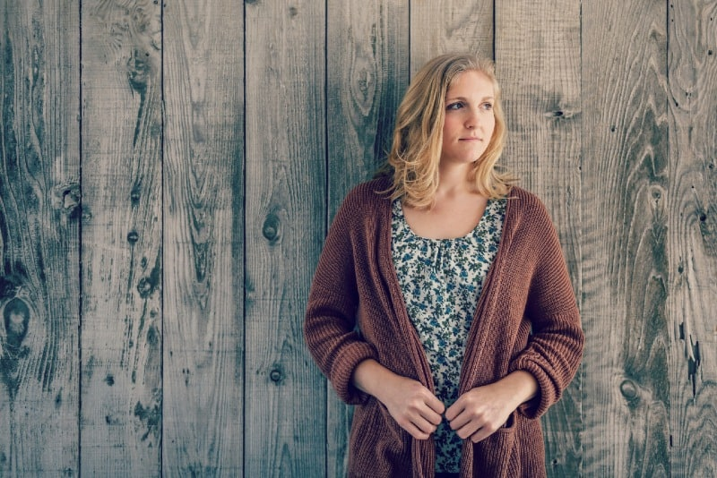 blonde woman in brown cardigan leaning on wooden wall