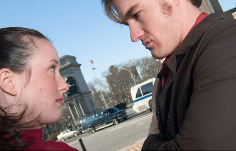 woman looking at a man eye to eye outdoors