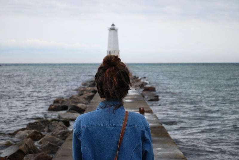 woman in denim shirt looking at lighthouse