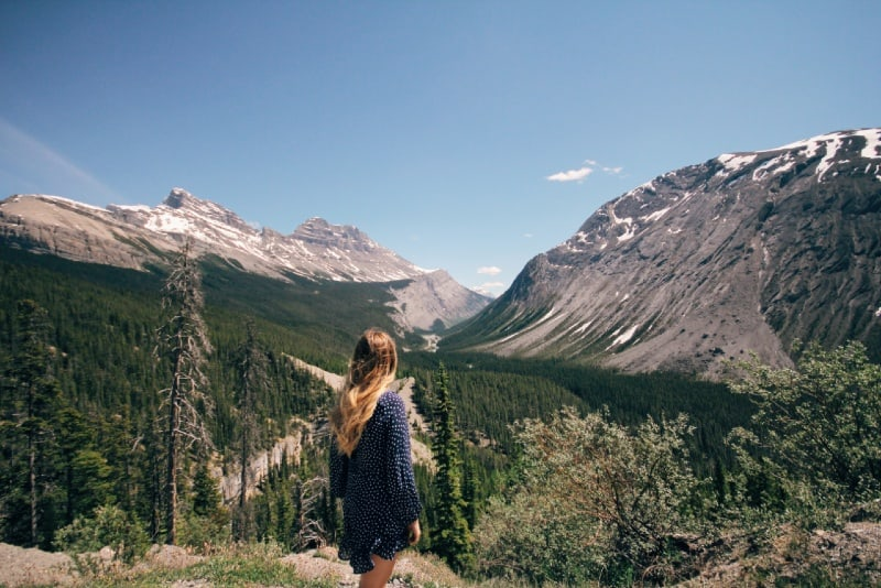 blonde woman in polka dot dress looking at mountains