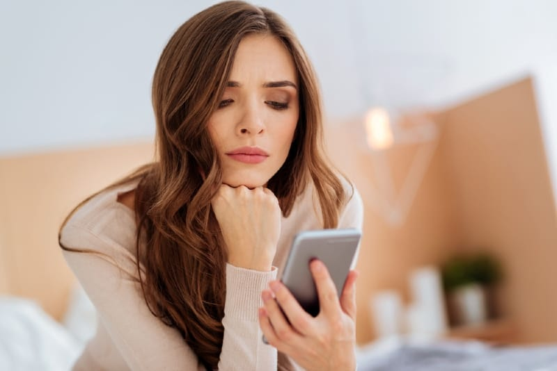 sad woman looking at phone while sitting indoor