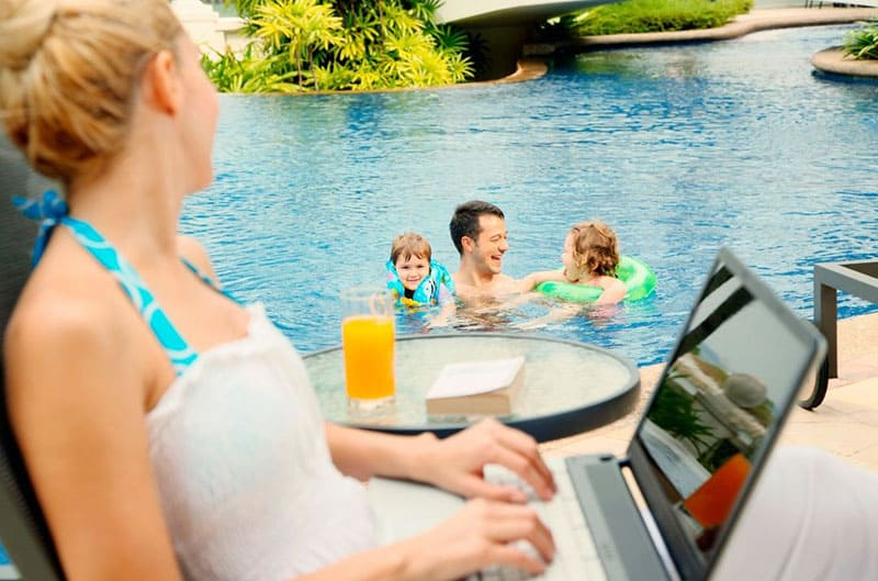 woman looking at her family enjoying at the pool while she is on her laptop