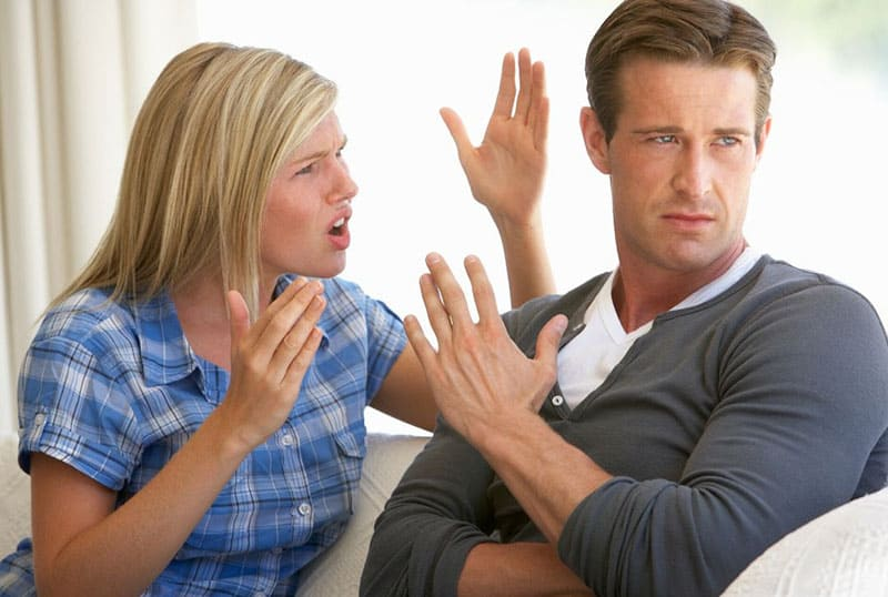 woman nagging and sitting next to a man trying to silence her