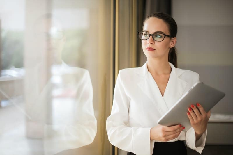 woman near glass window holding a tab standing inside the office premises