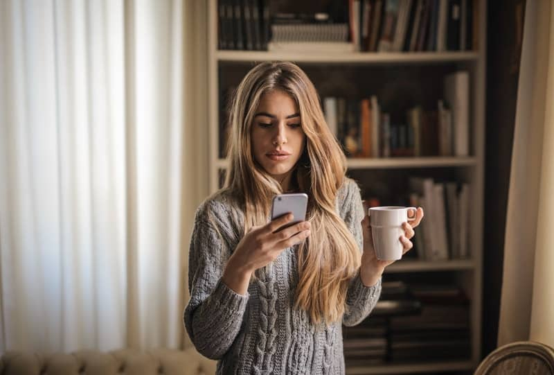 woman on cellphone holding a cup standing inside the living room