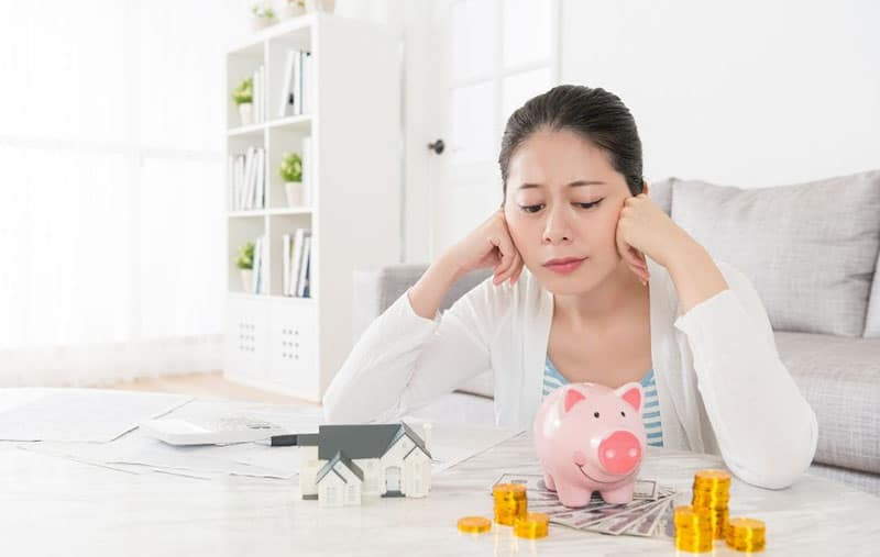 woman planning alone looking at the piggybank money and a small house in the table