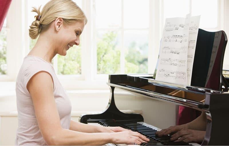 woman play piano smiling wearing white dress