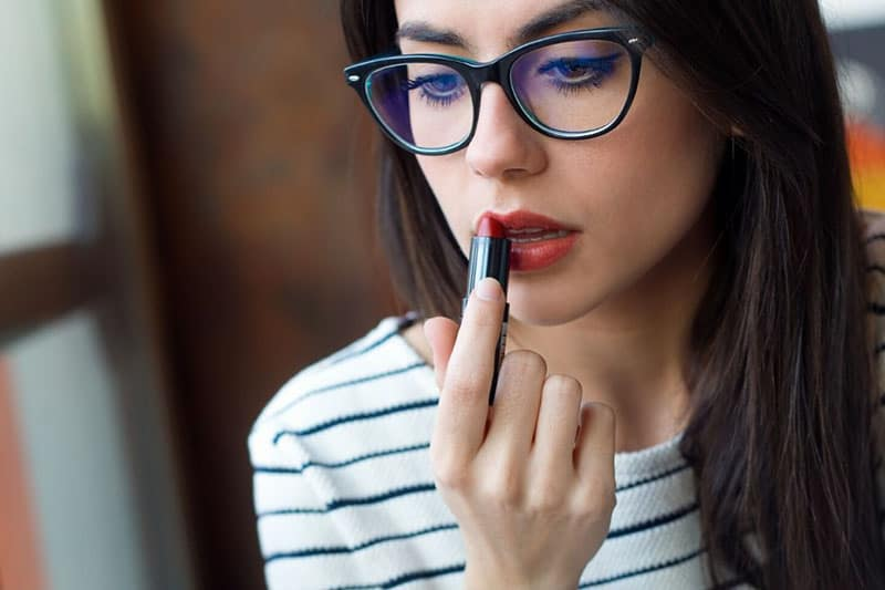 woman putting on lipstick wearing eyeglasses and stripe shirts