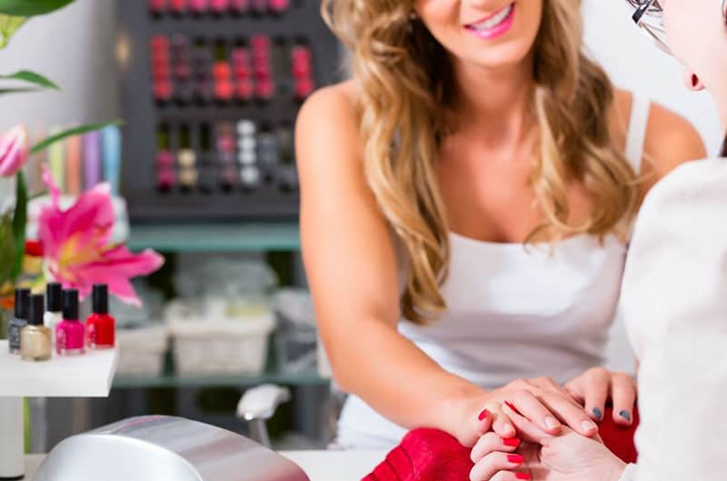 woman receiving manicure in a beauty parlor her nails being polished