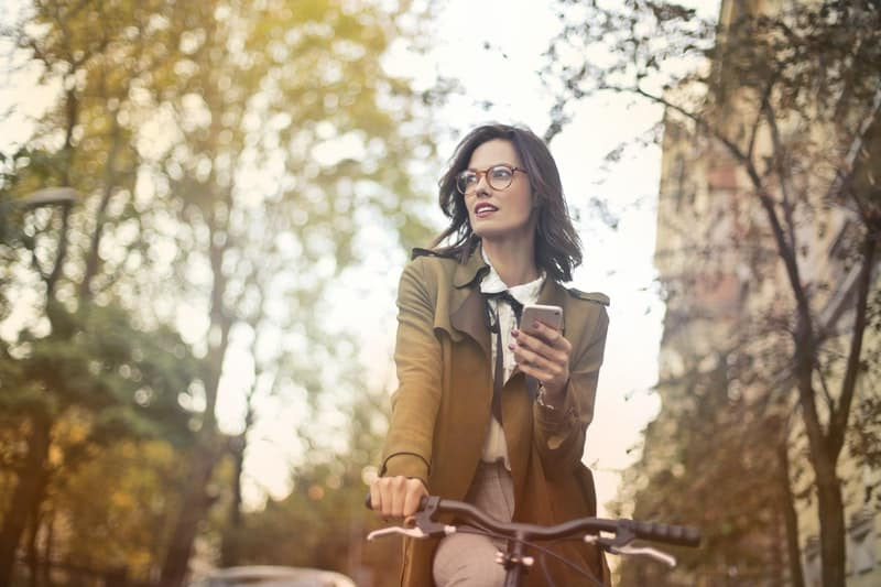 woman riding a bike while holding a smartphone in the middle of the road with many trees