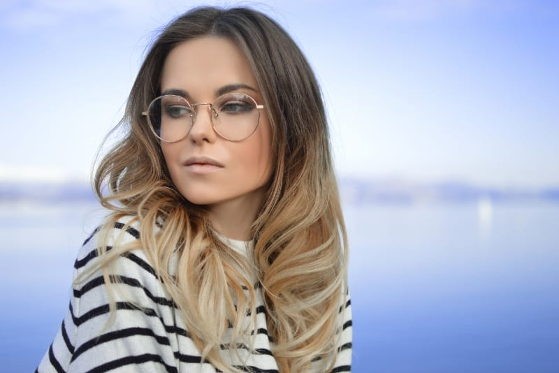 woman with round eyeglasses sitting near water
