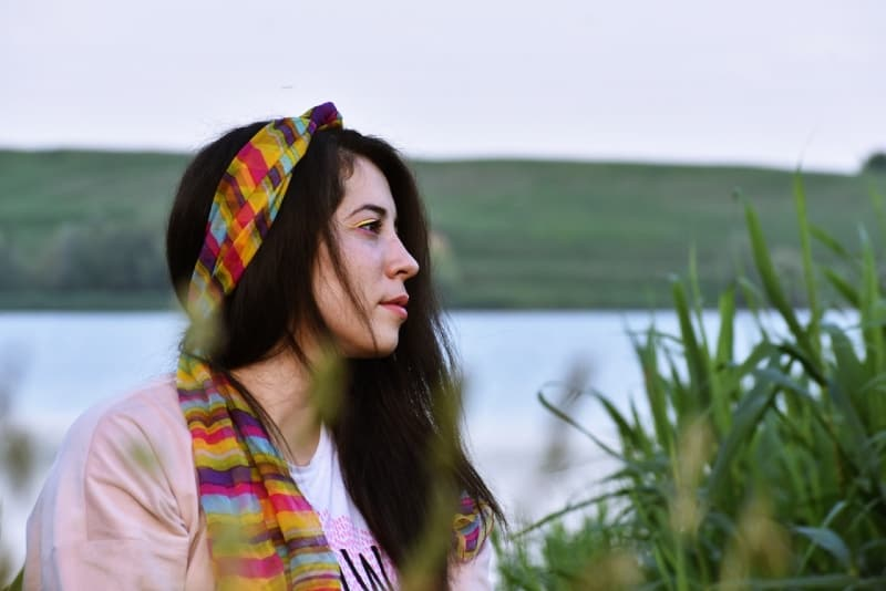 woman with colorful headscarf sitting near water