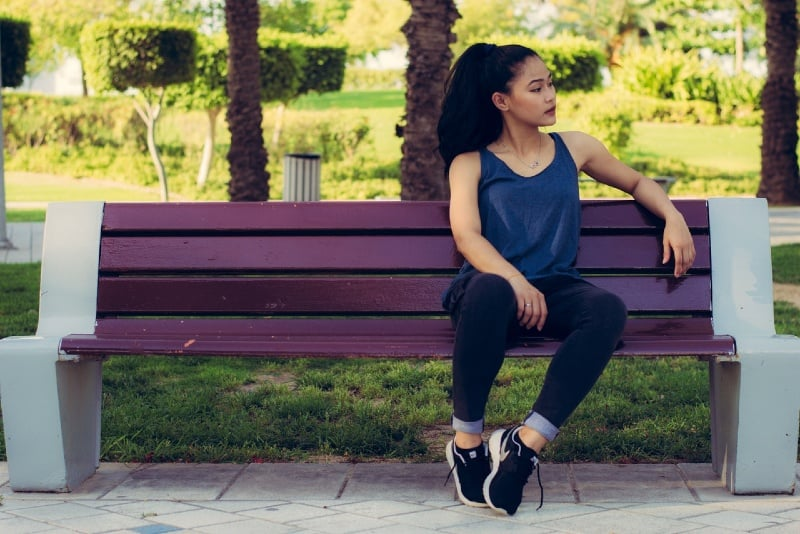 woman in black top sitting on purple bench