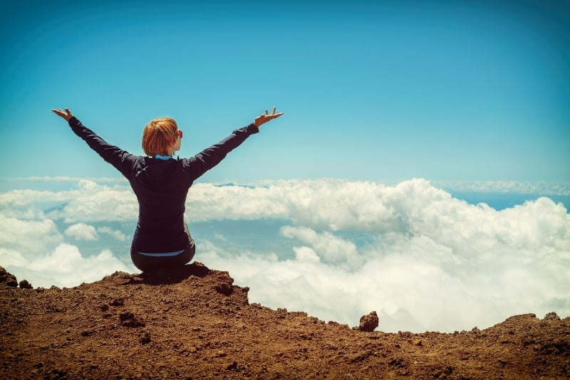 woman sitting on cliff raising up both hands