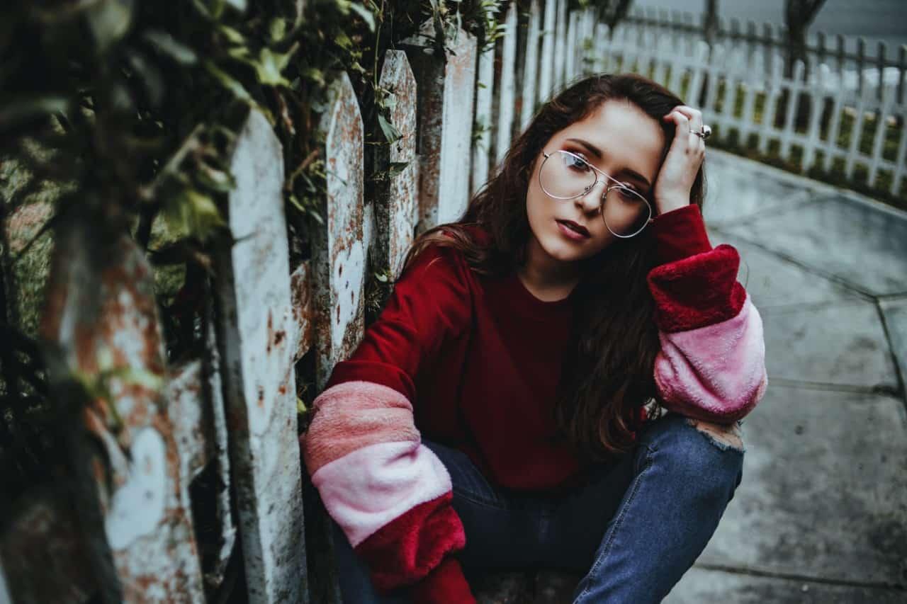 woman with eyeglasses sitting on concrete near fence