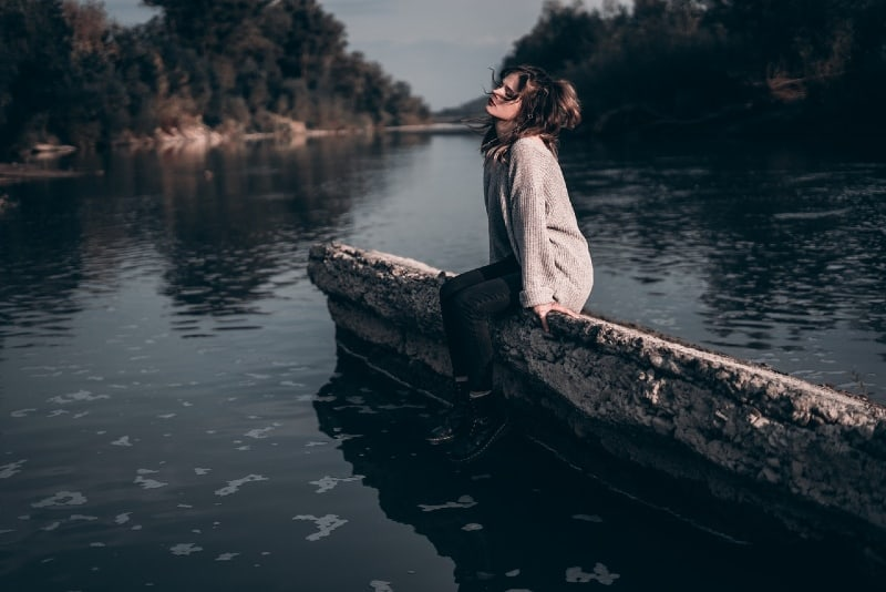 woman in gray sweater sitting on concrete near water